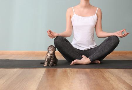 Foto de Young woman with cute kitten practicing yoga indoors - Imagen libre de derechos
