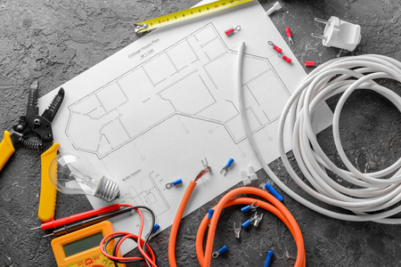 Photo for Electrician's supplies with house plan on grey background - Royalty Free Image