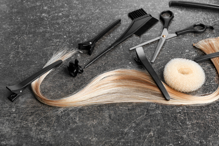 Foto per Professional hairdresser's set with strand of blonde hair on grey background - Immagine Royalty Free