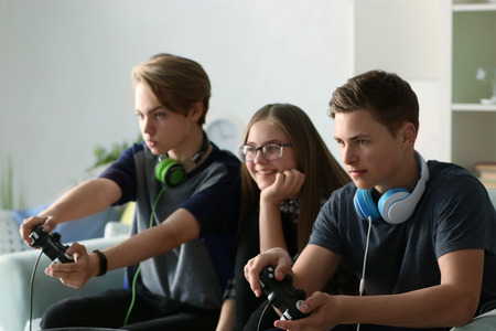 Photo pour Teenagers playing video games at home - image libre de droit