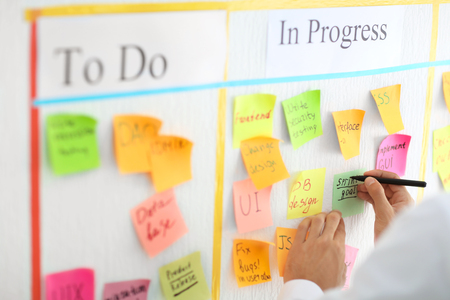 Photo pour Man writing on sticky note attached to scrum task board in office - image libre de droit