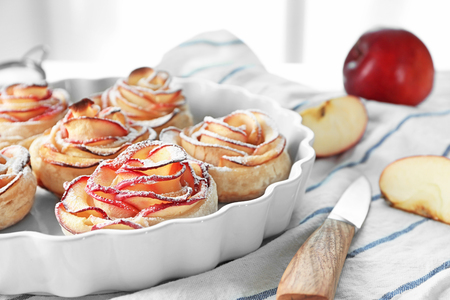 Photo pour Dish with tasty rose shaped apple pastry on table - image libre de droit