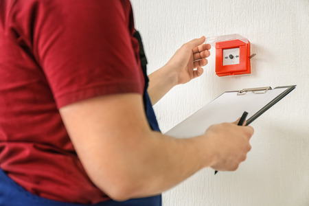 Photo pour Worker with clipboard near modern fire call point on wall - image libre de droit