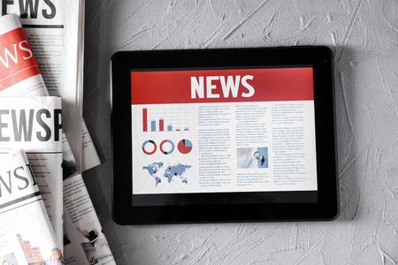 Foto de Tablet computer with news on screen on textured background - Imagen libre de derechos
