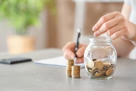 Photo pour Woman putting coins into glass jar on table. Savings concept - image libre de droit