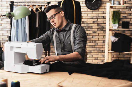 Photo for Young tailor working on sewing machine in atelier - Royalty Free Image