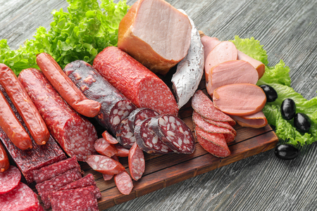 Photo for Assortment of delicious deli meats on wooden board - Royalty Free Image