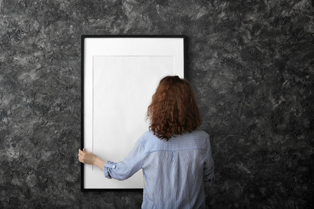 Photo pour Woman hanging blank photo frame on dark wall - image libre de droit