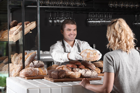 Photo pour Woman buying fresh bread from cheerful baker in shop - image libre de droit