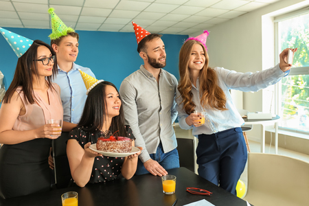 Foto de Young woman taking selfie with her colleagues at birthday party in office - Imagen libre de derechos