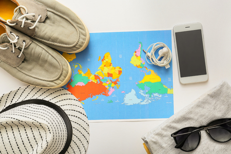 Photo pour Composition with world map, mobile phone, clothes and accessories on white background. Travel planning - image libre de droit