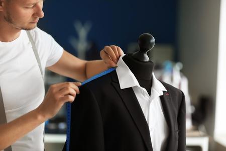 Photo pour Young tailor taking measurements of male jacket on mannequin in atelier - image libre de droit