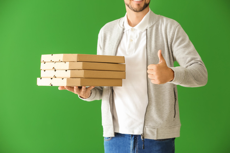 Photo pour Man with pizza boxes showing thumb-up gesture on color background. Food delivery service - image libre de droit
