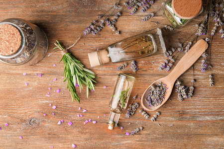 Photo pour Bottles of essential oil with lavender and rosemary on wooden table - image libre de droit