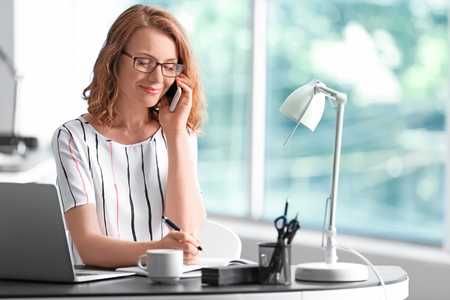 Photo pour Successful businesswoman talking by mobile phone in office - image libre de droit