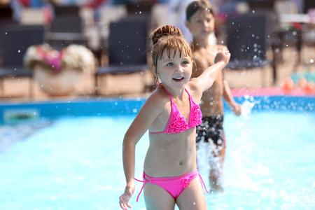 Foto de Cute girl playing in swimming pool on summer day - Imagen libre de derechos