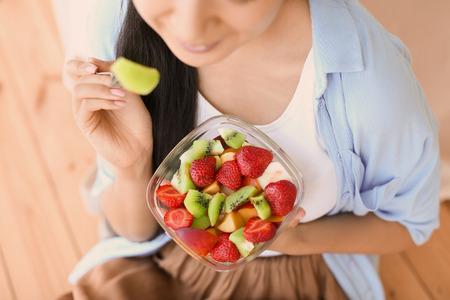 Foto de Woman eating healthy fruit salad at home, closeup - Imagen libre de derechos