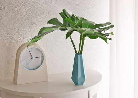 Photo pour Tropical leaves in vase with clock on table near light wall indoors - image libre de droit