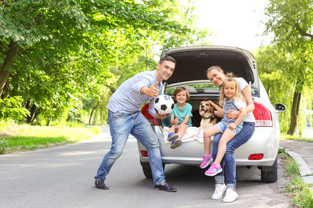 Photo pour Happy family with cute dog near car outdoors - image libre de droit