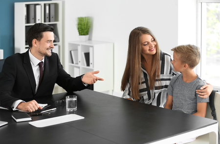 Photo pour Young woman and her son meeting with headmaster at school - image libre de droit