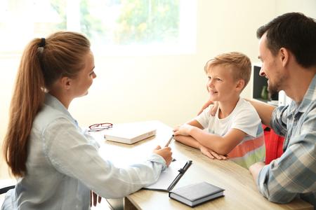 Foto de Young man and his son meeting with headmistress at school - Imagen libre de derechos