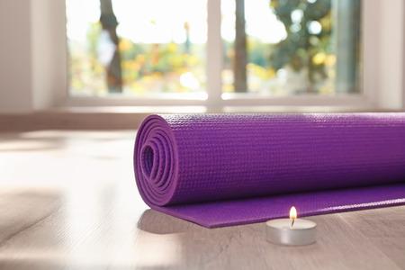 Foto de Yoga mat and  burning candle on floor - Imagen libre de derechos