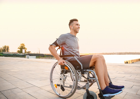 Photo pour Young man in wheelchair listening to music outdoors - image libre de droit