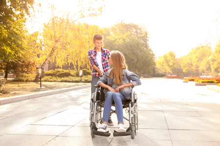 Photo pour Teenage girl in wheelchair and her brother outdoors - image libre de droit