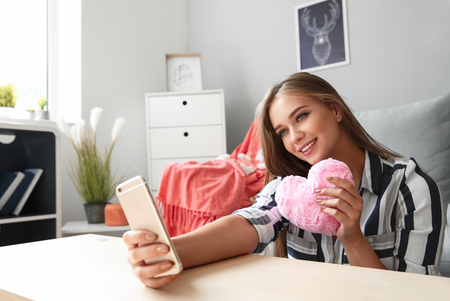 Foto de Young woman with mobile phone having online dating at home - Imagen libre de derechos