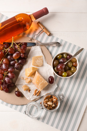 Photo pour Cheese and fresh grapes with bottle of wine on light table - image libre de droit