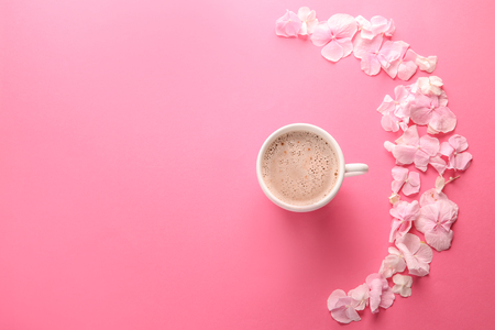 Foto de Beautiful flowers and cup of coffee on pink background - Imagen libre de derechos