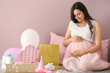 Foto de Beautiful pregnant woman with baby shower gifts at home - Imagen libre de derechos