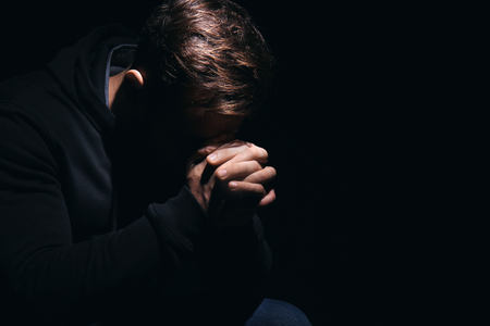 Photo for Religious young man praying to God on black background - Royalty Free Image