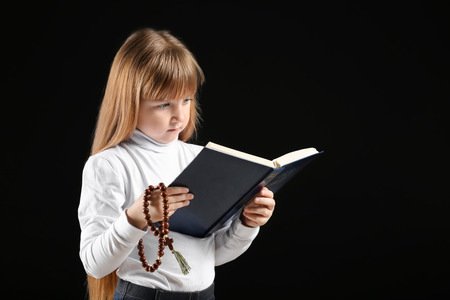 Photo for Little girl reading Bible on dark background - Royalty Free Image