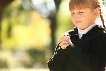 Photo for Little girl praying outdoors - Royalty Free Image