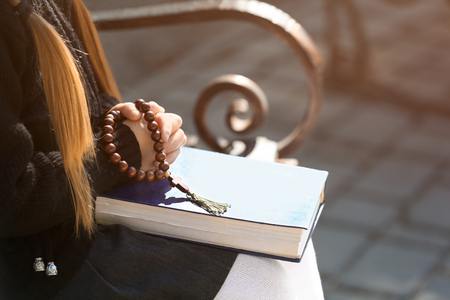 Photo for Little girl with Bible praying on bench outdoors - Royalty Free Image