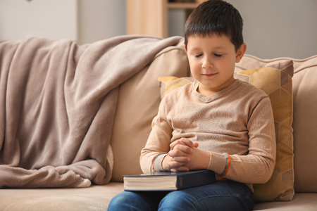 Photo for Little boy with Bible praying at home - Royalty Free Image