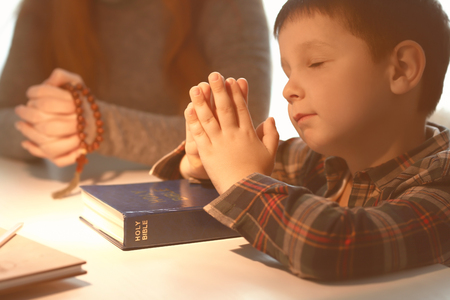 Photo for Little boy and his mother praying at home - Royalty Free Image