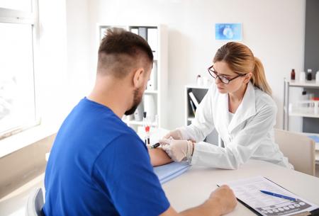 Foto de Female doctor drawing a blood sample of male patient in clinic - Imagen libre de derechos