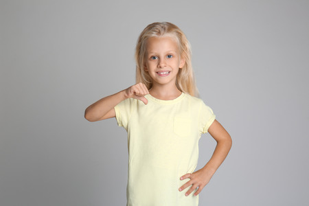 Photo for Cute little girl pointing at her t-shirt on grey background - Royalty Free Image