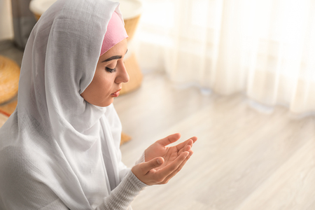 Photo for Young Muslim woman praying at home - Royalty Free Image