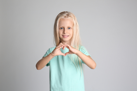 Photo for Cute little girl in t-shirt making heart with her hands on grey background - Royalty Free Image