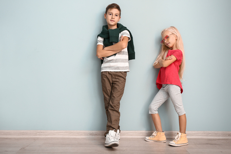 Foto de Cute boy and girl in fashionable clothes near color wall - Imagen libre de derechos
