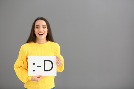 Photo pour Young woman holding sheet of paper with drawn emoticon on grey background - image libre de droit