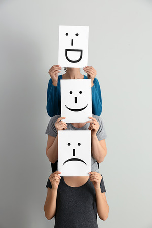 Photo pour Young women hiding faces behind sheets of paper with drawn emoticons on light background - image libre de droit
