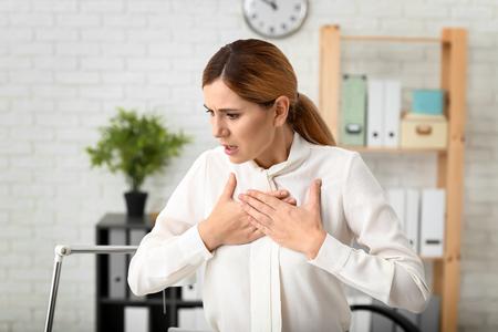 Photo pour Woman having panic attack at workplace - image libre de droit