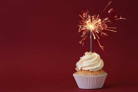 Foto de Delicious cupcake with sparkler on color background - Imagen libre de derechos
