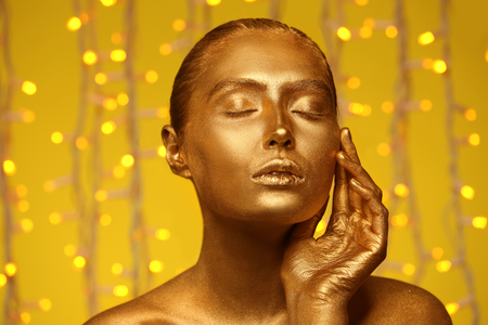 Photo for Beautiful young woman with golden paint on her body against defocused lights - Royalty Free Image