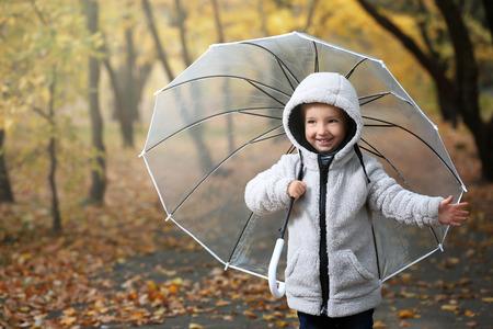 Foto de Cute little boy with transparent umbrella in autumn park - Imagen libre de derechos