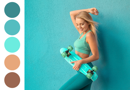 Photo pour Sporty woman with skateboard near color wall. Different color patterns - image libre de droit